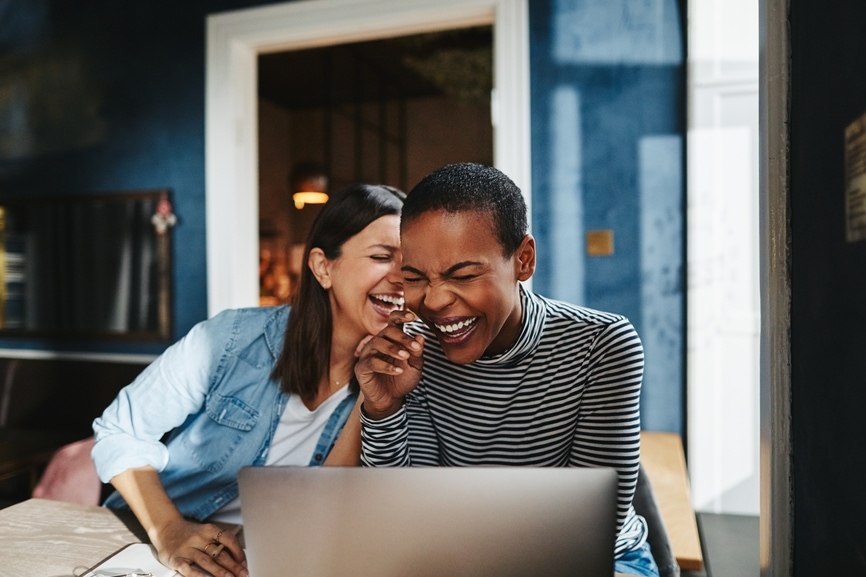 Two diverse young female entrepreneurs laughing while working together at a table in a cafe